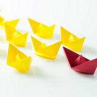 Leadership concept with a red paper ship leading among yelllow ships